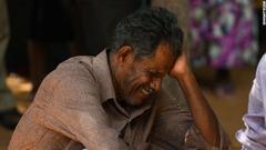 病院の外で涙を流す被害者の家族=バティカロア