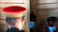 遺体安置所のドア付近に立つ病院職員や兵士