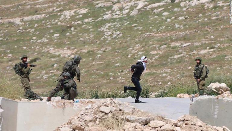 後ろ手に手錠をかけられ、目隠しをされた状態でイスラエル兵士から逃げようとする少年/Courtesy Mohammad Hmeid