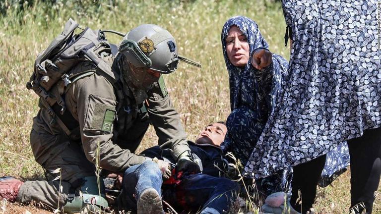 銃撃直後、兵士は少年を拘束して手当てを施した/Mohammed Hmeid/AFP/Getty Images