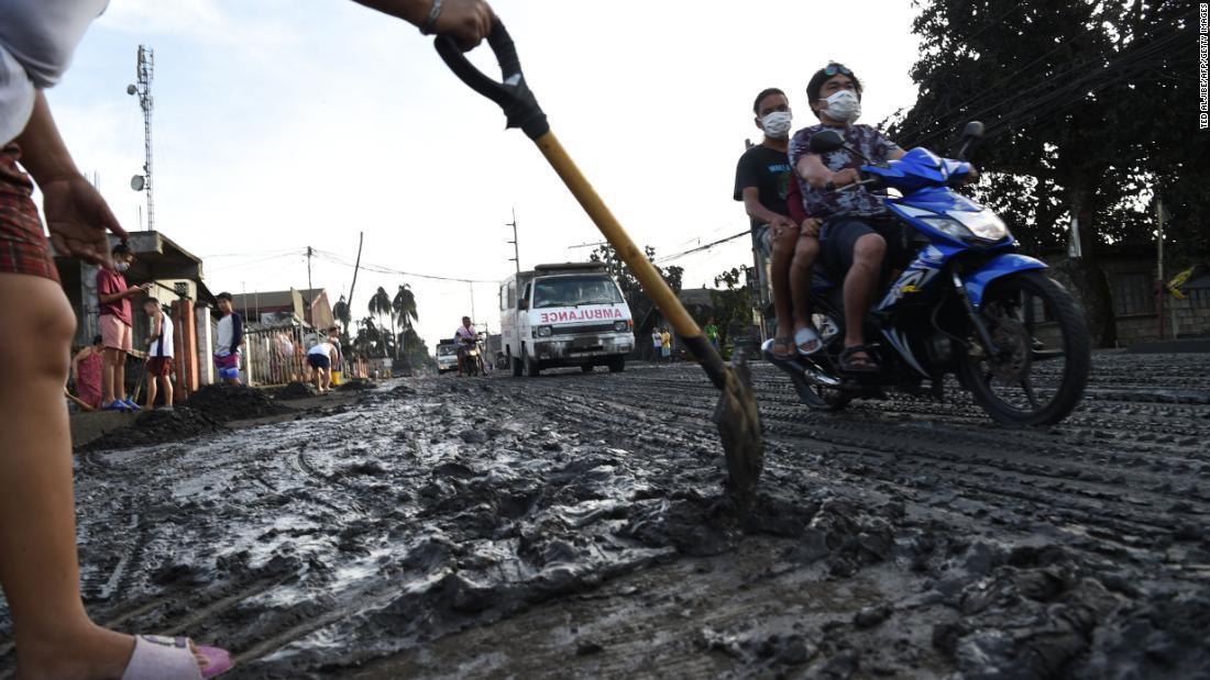 住民が泥や灰を除去する様子=13日、タナウアン/Ted Aljibe/AFP/Getty Images