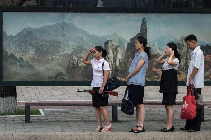 平壌の街路でバスを待つ人々/Ed Jones/AFP/Getty Images