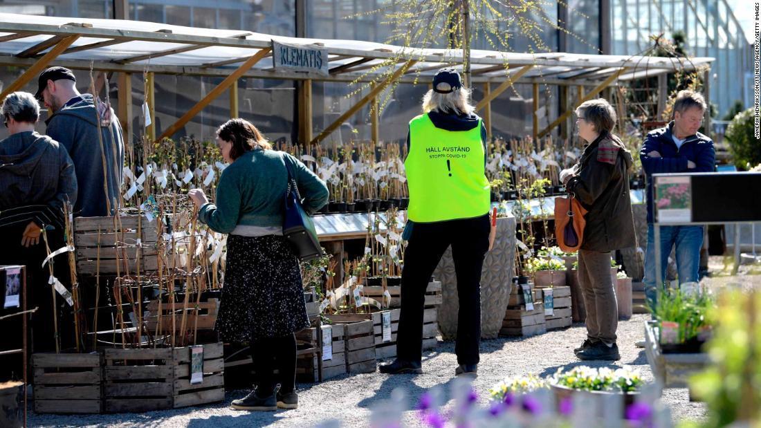 園芸用品店で「距離を取って。ストップ、新型コロナウイルス」とかかれたベストを着用する従業員/JANERIK HENRIKSSON/TT News Agency/Getty Images