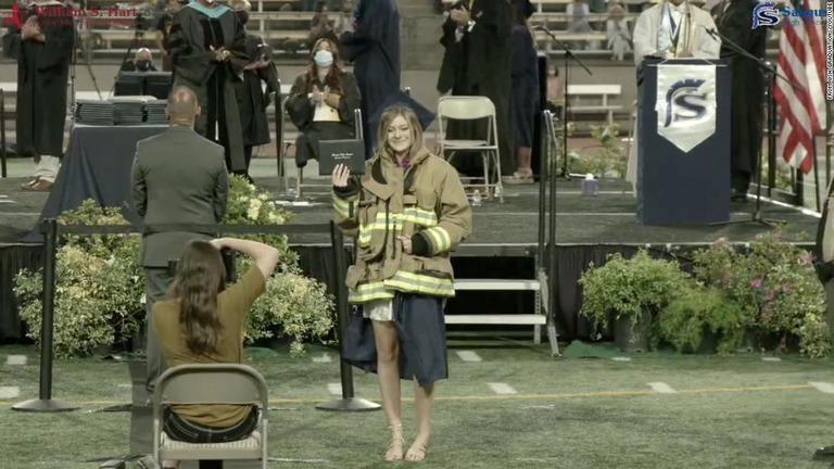 亡き父の消防士用ジャケットを身に着けて卒業証書を受け取るジョスリン・カーロンさん/From WSH Graduations/YouTube