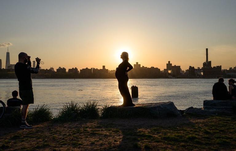 ニューヨーク・ブルックリンで夕日を背景に写真に収まる妊婦/Ed Jones/AFP/Getty Images