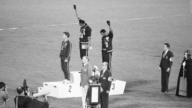 1968年大会の表彰台で黒人差別に抗議し拳を高く掲げる「ブラック ...
